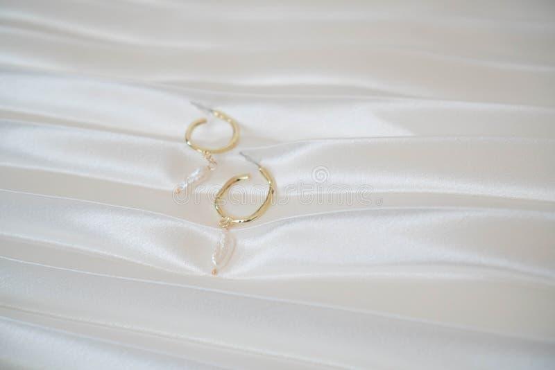 Gli orecchini rotondi dell'oro con le perle si trovano su un fondo bianco coperto del raso Accessorio alla moda di estate dell'or fotografia stock libera da diritti