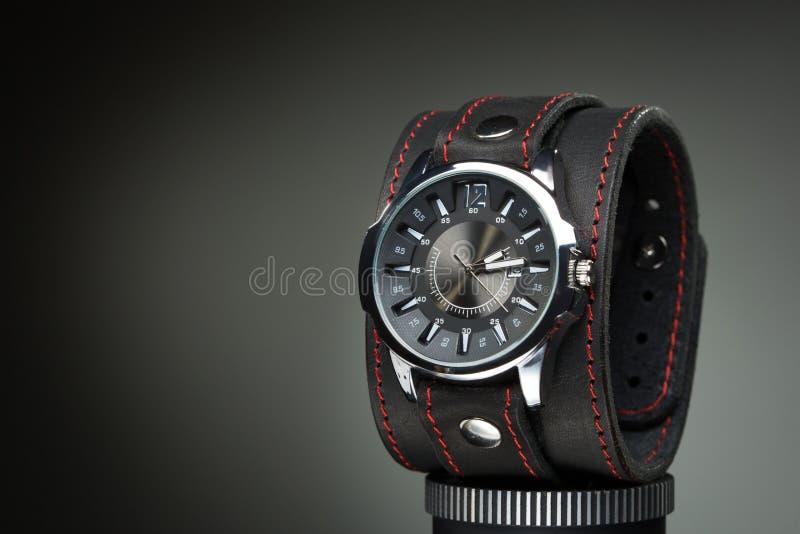 Gli orologi degli uomini con l'ampio braccialetto di cuoio immagini stock