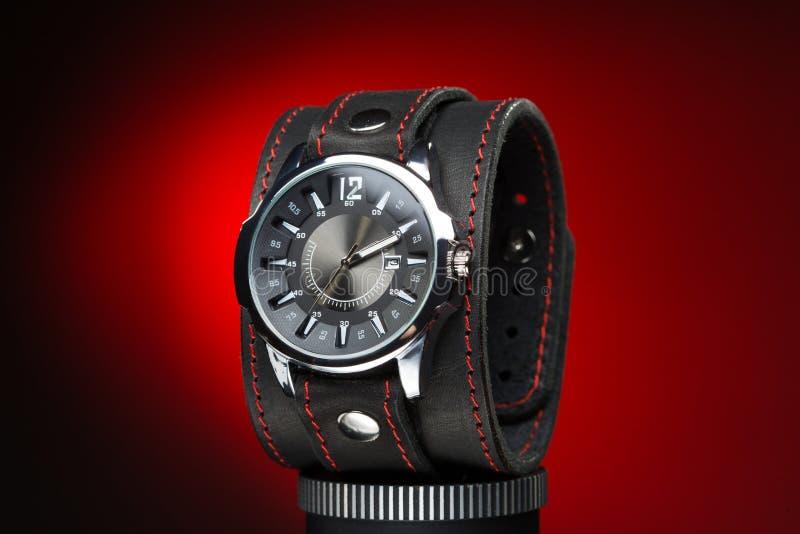 Gli orologi degli uomini con l'ampio braccialetto di cuoio fotografia stock