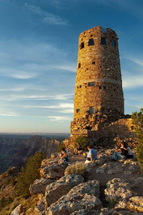 Gli ospiti esaminano fuori Grand Canyon accanto al posto di guardia di pietra nel parco nazionale di Grand Canyon fotografia stock libera da diritti