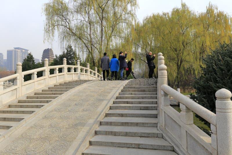 Gli ospiti stanno sul ponte di pietra dell'arco del museo nell'inverno, adobe rgb di xian fotografia stock libera da diritti