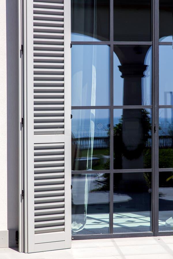 Gli otturatori di legno di legno grigio sono aperti a luce solare immagini stock