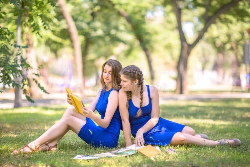 Gli ragazza-studenti incantanti, bei e giovani leggono i libri e sembrano felici nel parco Due ragazze che leggono un libro fotografia stock libera da diritti