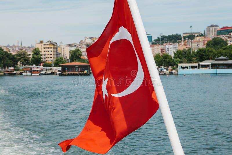 Gli sbattimenti nazionali della bandiera del turco nel vento contro il contesto del Bosphorus e di Costantinopoli vaghi in fotografie stock libere da diritti
