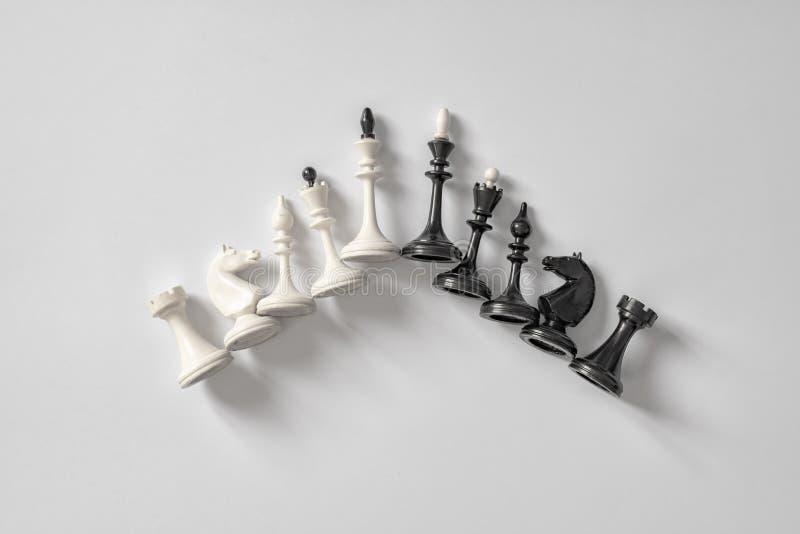 Gli scacchi in bianco e nero dipendono il fondo bianco Copi lo spazio per la vostra iscrizione fotografia stock libera da diritti