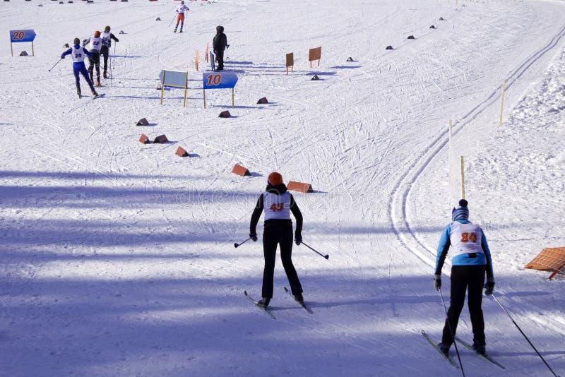Gli sciatori attraversano il pendio dello sci prima dell'inizio fotografia stock libera da diritti