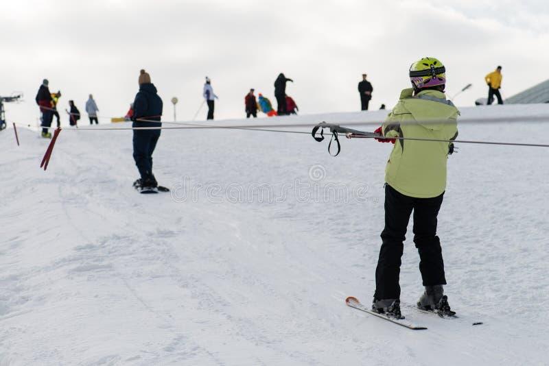 Gli sciatori e gli snowboarders guidano l'alzare la montagna fotografia stock libera da diritti