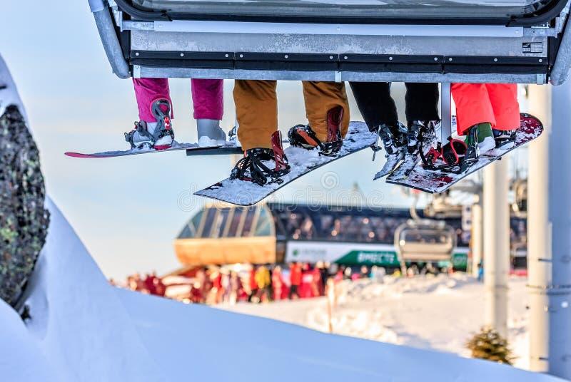 Gli sciatori e gli snowboarders guidano sull'ascensore di sci della sedia alla stazione sciistica in Soci, Russia della montagna  fotografia stock libera da diritti