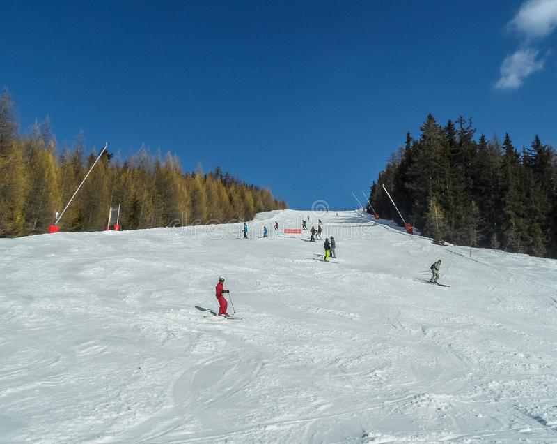 Gli sciatori e gli snowboarders nei pendii dello sci delle montagne della località di soggiorno Les si arca, la Francia fotografia stock libera da diritti