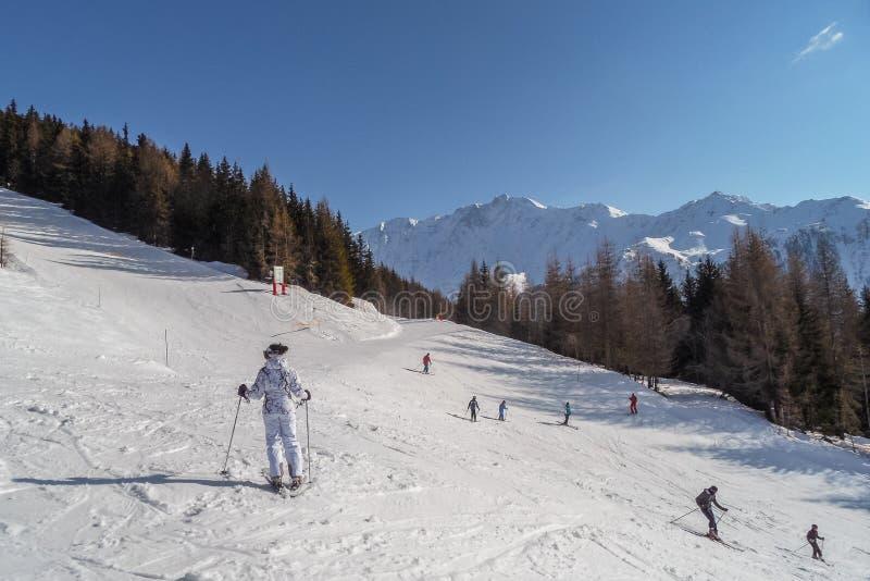 Gli sciatori e gli snowboarders nei pendii dello sci delle montagne della località di soggiorno Les si arca, la Francia immagine stock