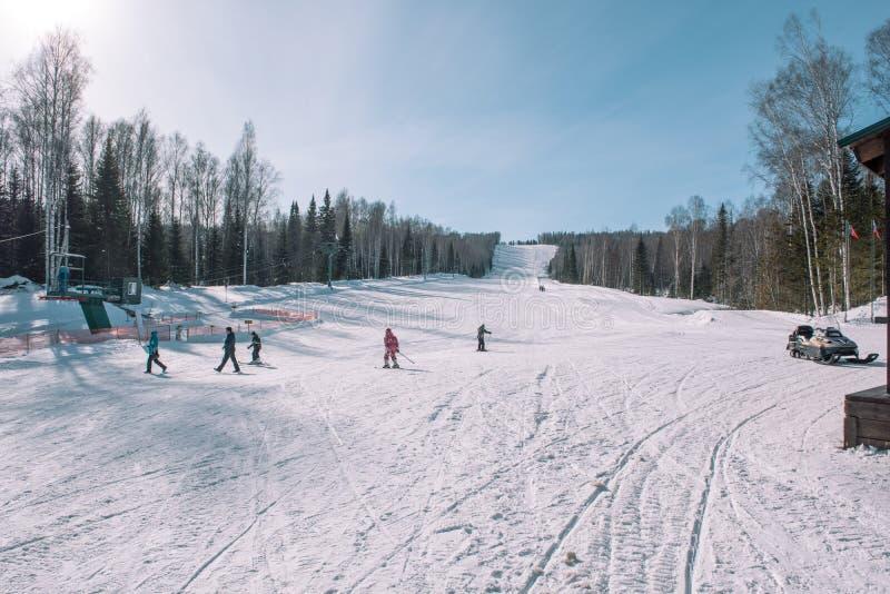 Gli sciatori guidano dalla montagna Stazione sciistica Inverno in Siberia Paesaggio di inverno Bella natura immagini stock libere da diritti