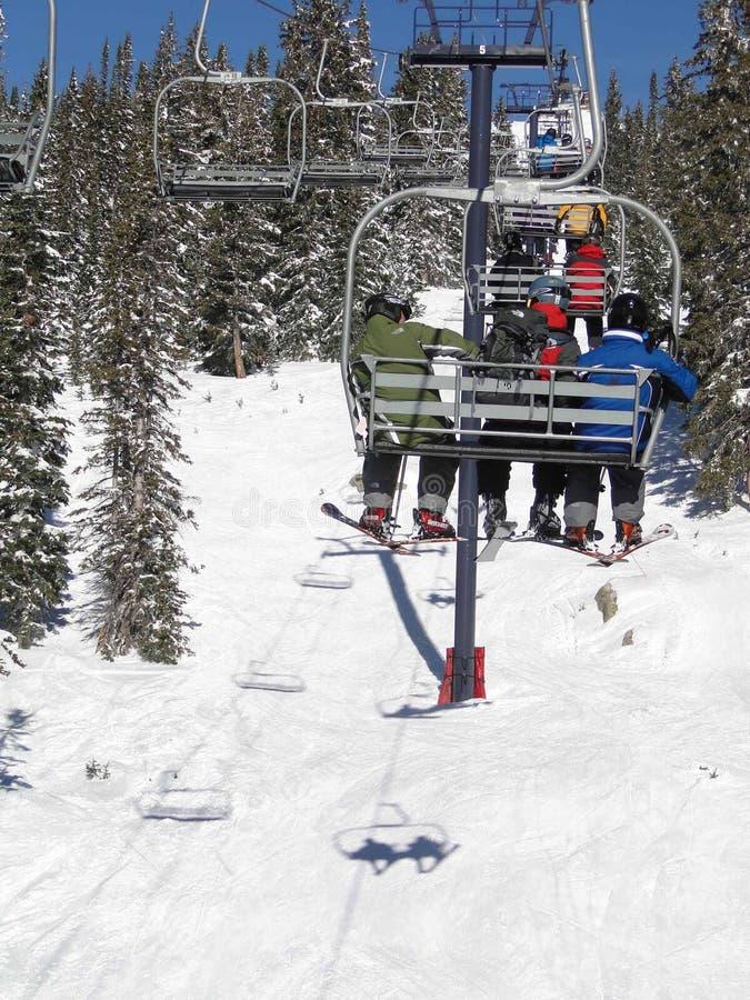 Gli sciatori guidano la seggiovia attraverso una foresta attillata fotografie stock