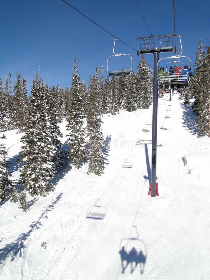 Gli sciatori guidano la seggiovia attraverso una foresta attillata fotografie stock libere da diritti