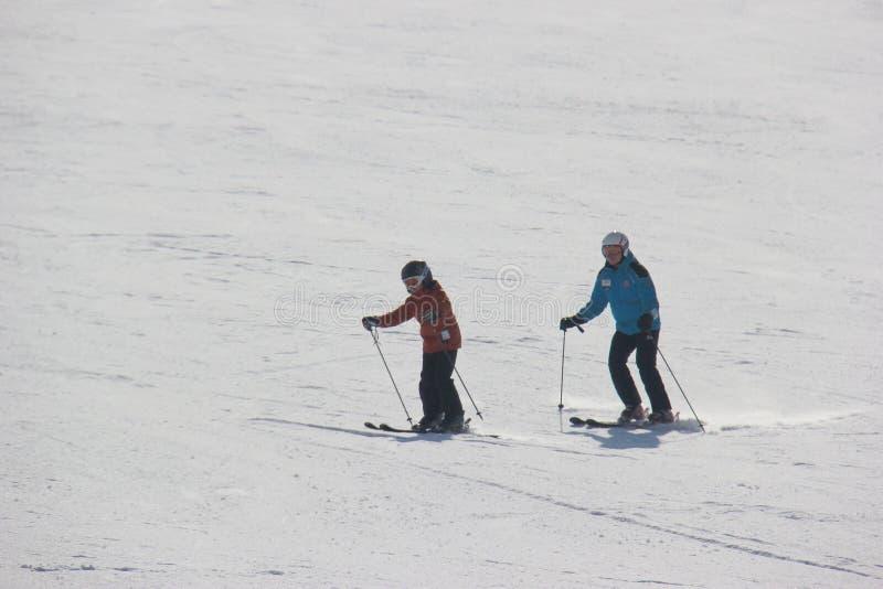 Gli sciatori stanno sciando in discesa fotografie stock