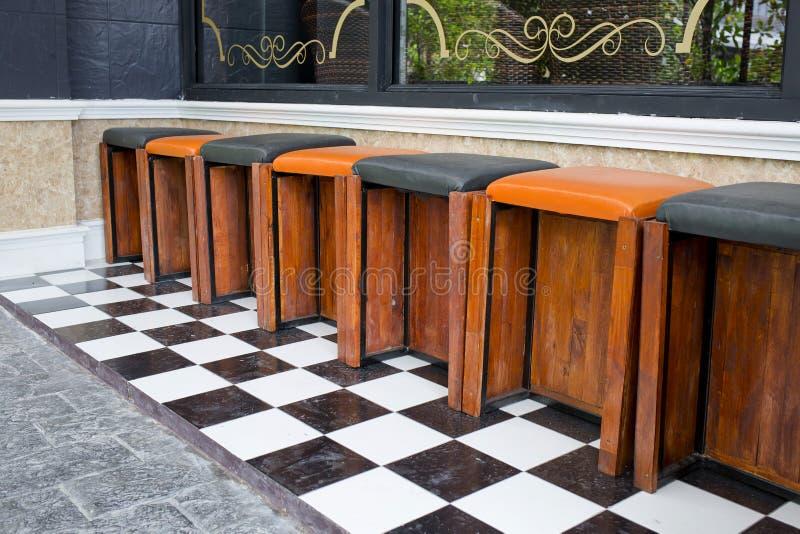 Gli sgabelli da bar di legno classici sono allineati ad una barra