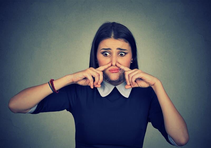 Gli sguardi del naso di pizzichi della donna con repulsione qualcosa puzza il cattivo odore fotografie stock libere da diritti