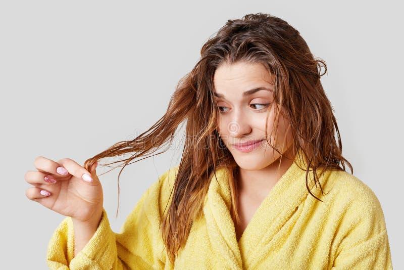 Gli sguardi femminili adorabili alle doppie punte dopo la presa della doccia, ha danneggiato i capelli, indossa i vestiti domesti fotografie stock libere da diritti