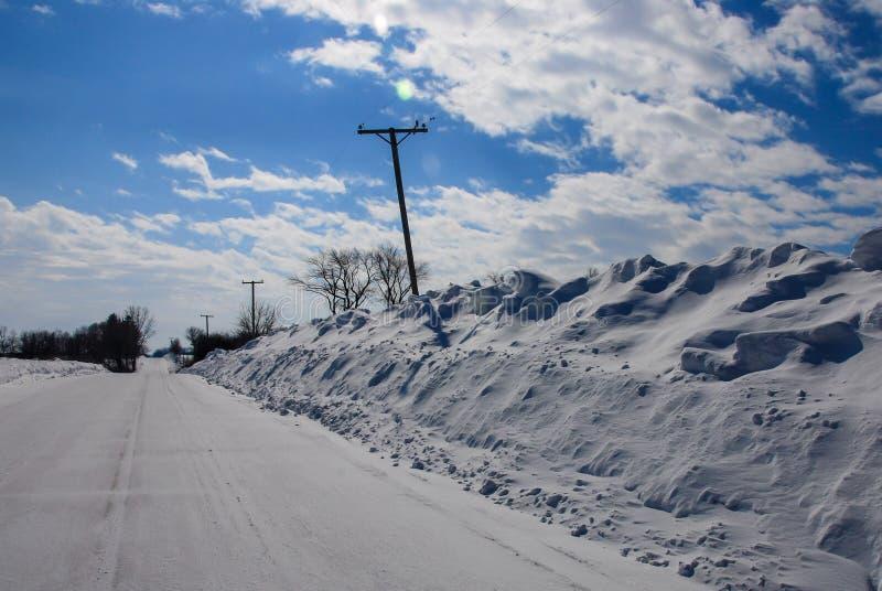 Gli snowbanks estremamente profondi hanno spinto il palo di telefono curvato immagine stock libera da diritti