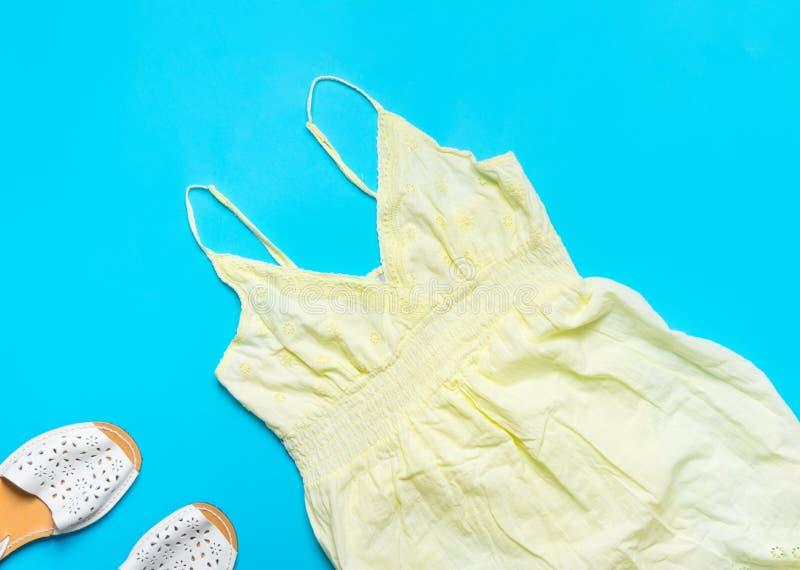 Gli spaghetti attaccano il vestito dall'estate delle donne del cotone con pizzo che orla i sandali di cuoio bianchi sul fondo blu immagine stock libera da diritti