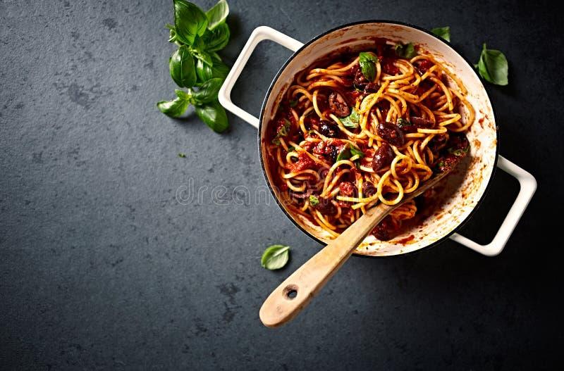 Gli spaghetti con salsa al pomodoro, le olive di Kalamata ed il basilico freschi in una cottura filtrano visto da sopra immagine stock