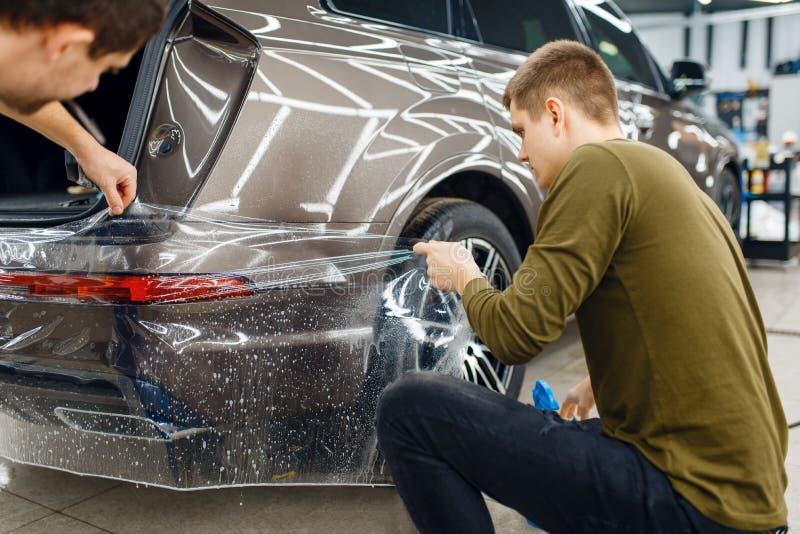 Gli specialisti applicano film per la protezione dell'auto sul paraurti immagini stock libere da diritti
