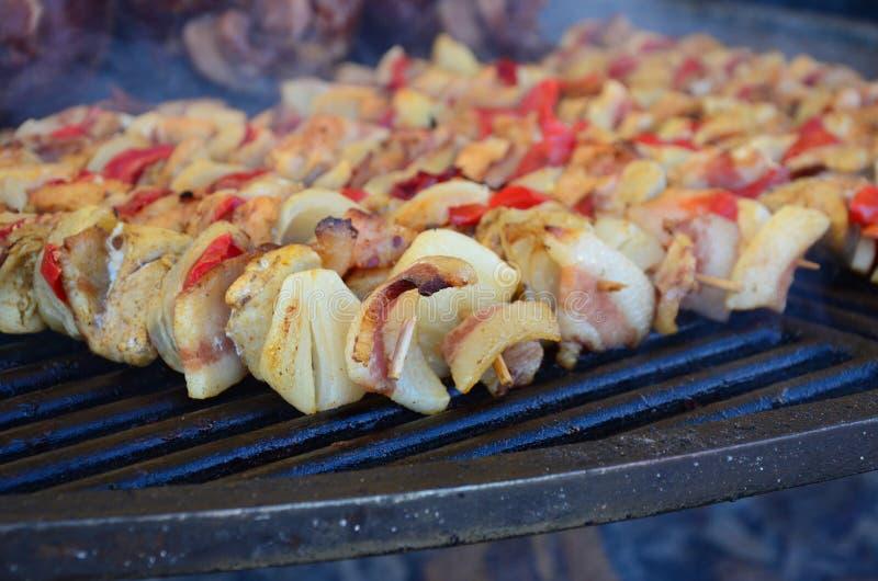 Gli spiedi sul bastone di legno con la carne suina e le verdure saporite si mescolano fotografia stock