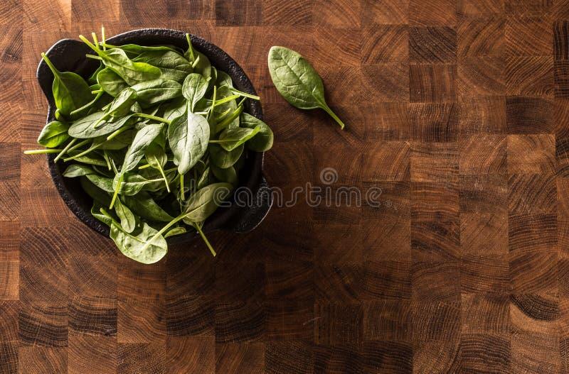 Gli spinaci freschi del bambino lasciano in ciotola sul bordo di macellaio immagini stock libere da diritti