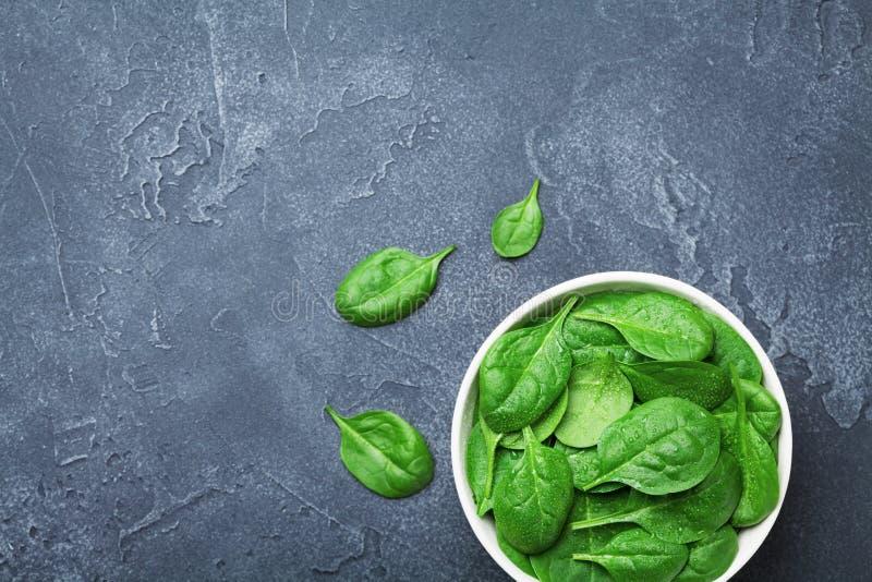 Gli spinaci verdi lasciano in ciotola sulla tavola nera da sopra Alimento biologico fotografia stock libera da diritti