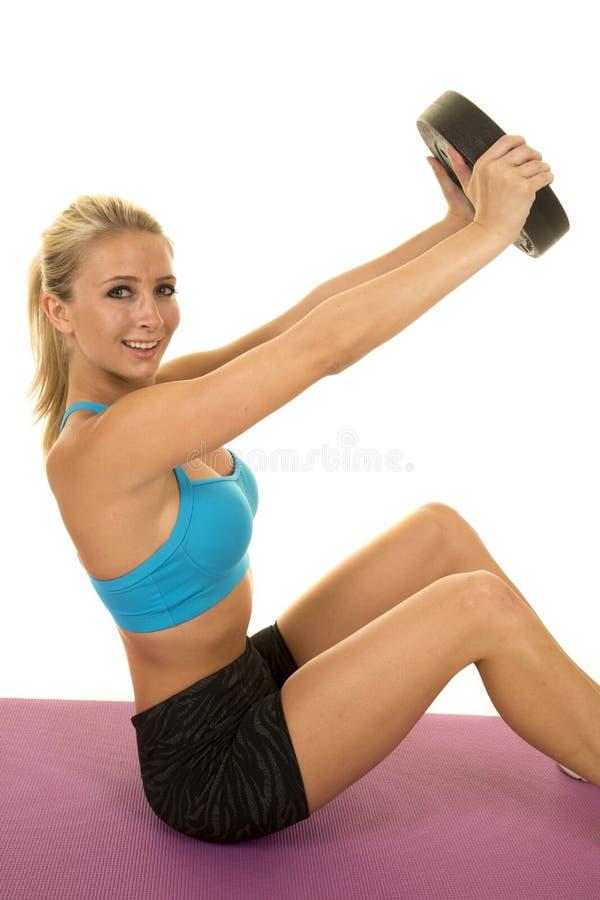 Gli sport che biondi del blu della donna il reggiseno si siede pesano lo sguardo da vicino fotografia stock