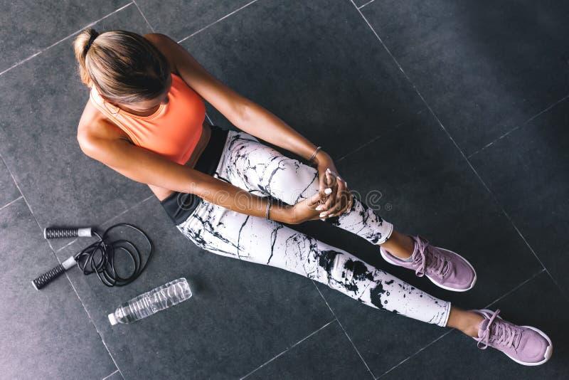 Gli sport d'uso di modello di modo indossano fare l'esercizio al pavimento nero fotografia stock libera da diritti