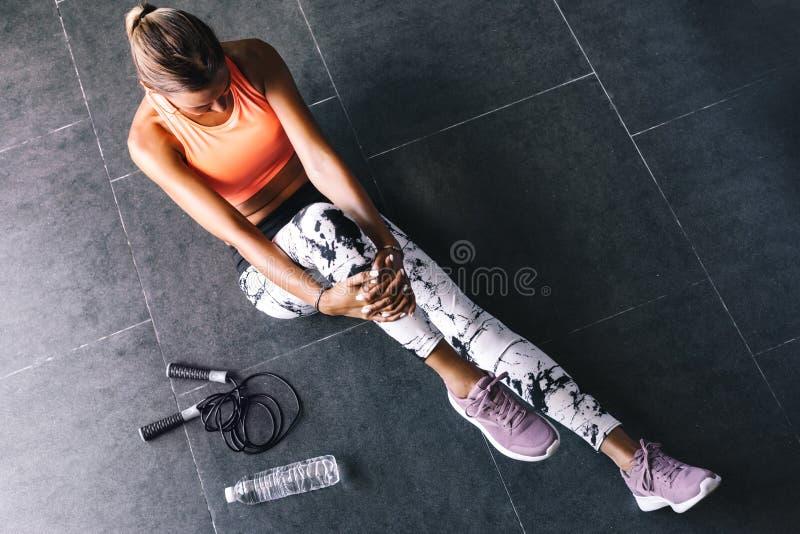 Gli sport d'uso di modello di modo indossano fare l'esercizio al pavimento nero immagine stock libera da diritti
