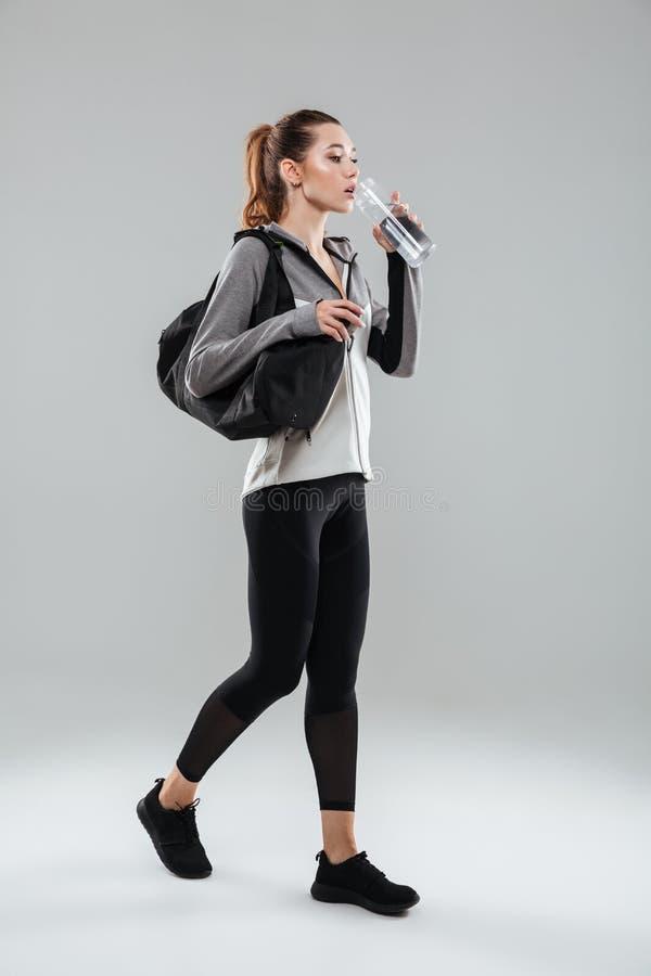 Gli sport di trasporto della giovane donna graziosa di forma fisica insaccano ed acqua potabile fotografia stock