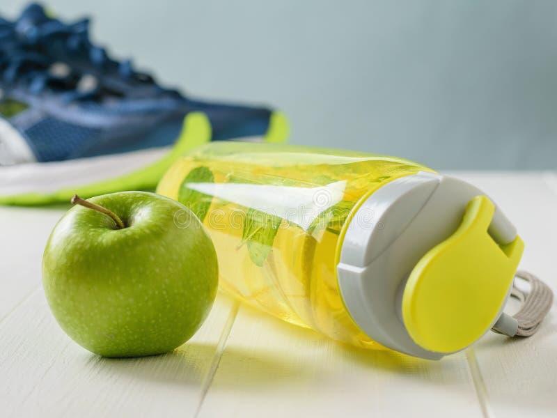 Gli sport imbottigliano con una bevanda di rinfresco e Apple verde sui precedenti delle scarpe da corsa fotografia stock