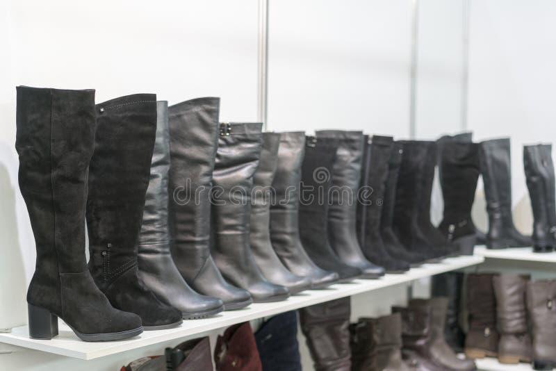 gli stivali delle donne sugli scaffali nel deposito Padiglione del deposito con le scarpe delle donne alla moda Stivali di cuoio  fotografia stock