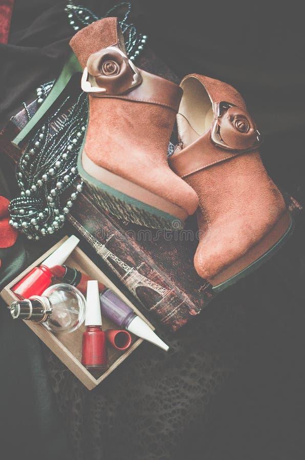 Gli stivali marroni della caviglia della pelle scamosciata si trovano su un fondo scuro Accanto alla scatola con gli accessori de immagine stock libera da diritti