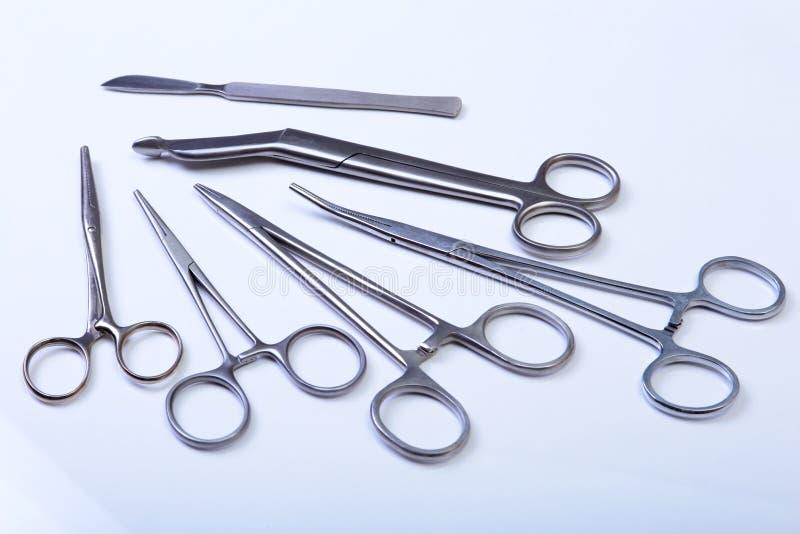 Gli strumenti chirurgici e gli strumenti compreso i bisturi, pinzette del forcipe hanno sistemato su una tavola per chirurgia fotografie stock libere da diritti