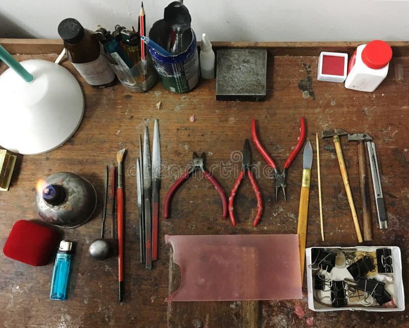Gli strumenti del creatore dell'oro sulla tavola di legno con la traccia di melten l'acrilico immagini stock