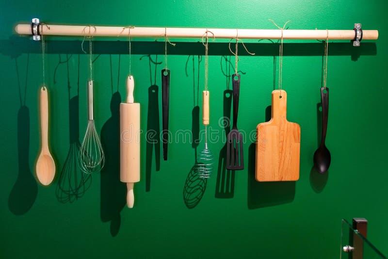 Gli strumenti di legno e di plastica della cucina appendono sui ganci fotografie stock