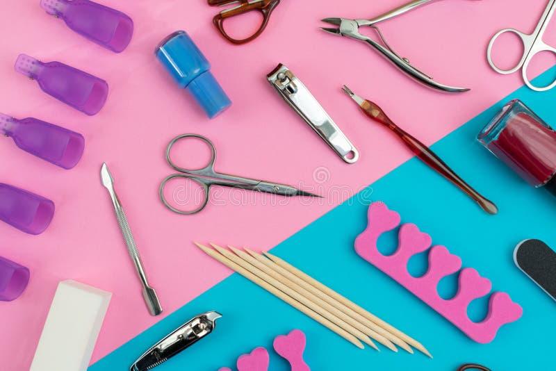 Gli strumenti di pedicure o del manicure hanno sparso su un fondo rosa e blu immagini stock libere da diritti