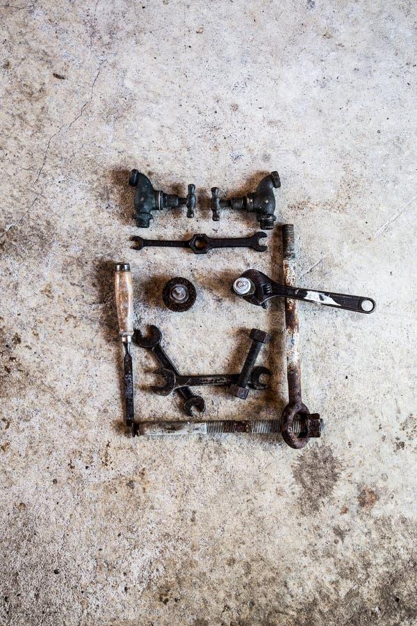 Gli strumenti e le parti hanno sistemato sotto forma di un fronte sorridente su cemento immagine stock