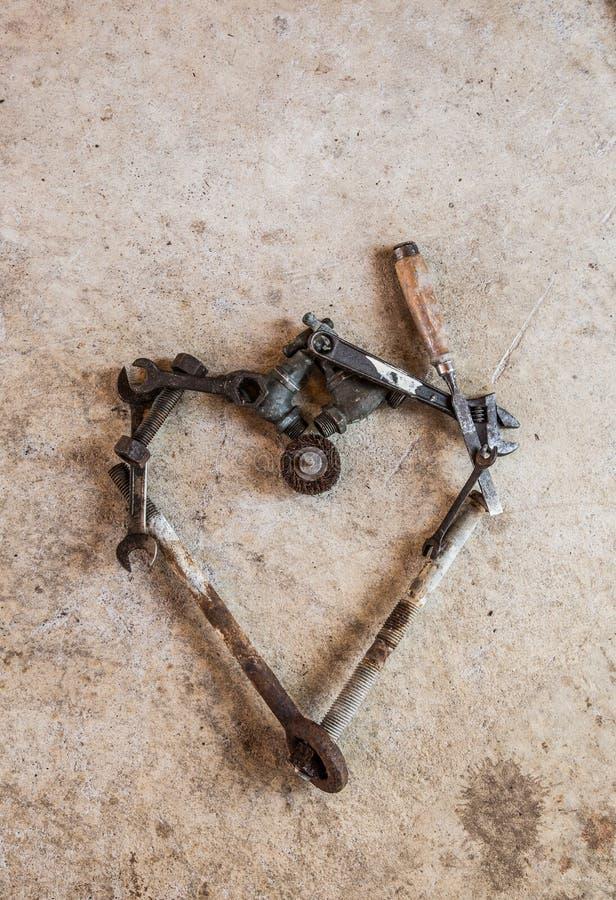 Gli strumenti e le parti hanno sistemato in un cuore di amore su cemento immagini stock