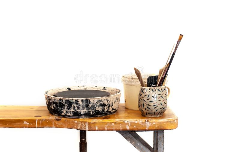 Gli strumenti per terraglie con il tornio da vasaio stanno stando sulla tavola di legno in studio sudicio, bianco isolato immagini stock libere da diritti