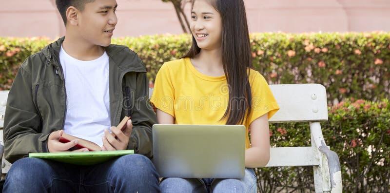 Gli studenti adolescenti lavorano il lavoro della scuola sul computer portatile immagini stock libere da diritti