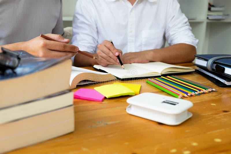 Gli studenti aiuta l'amico che insegna e che impara a supplementare tematico in biblioteca Concetto di formazione fotografia stock libera da diritti