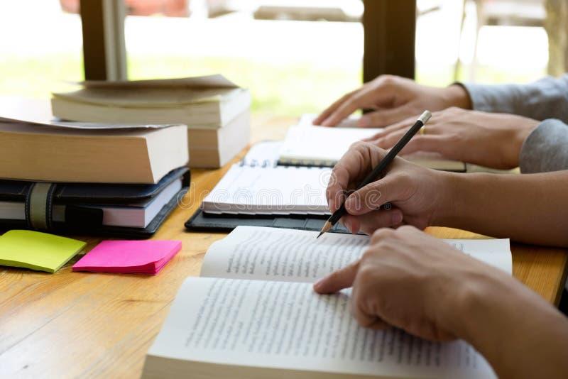 Gli studenti aiuta l'amico che insegna e che impara a supplementare tematico in biblioteca facendo uso della compressa all'istruz fotografia stock