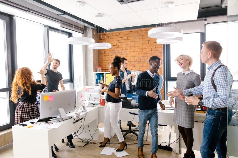 Gli studenti allegri team facendo il livello cinque in ufficio creativo immagini stock libere da diritti