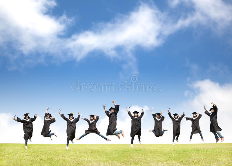 Gli studenti celebrano la graduazione ed il salto felice fotografia stock libera da diritti