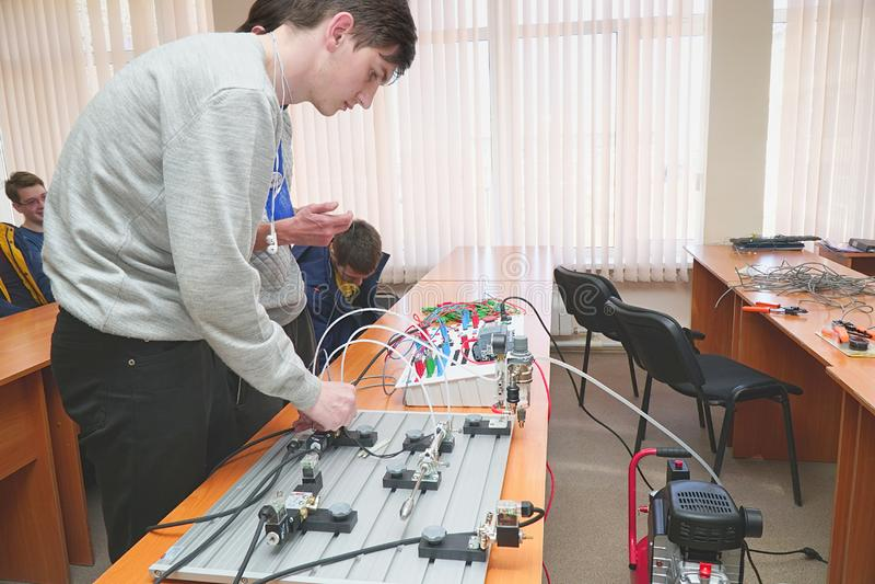 Gli studenti collegano il pannello di controllo dei cavi con il piccolo banco di prova per gli esperimenti fotografia stock libera da diritti