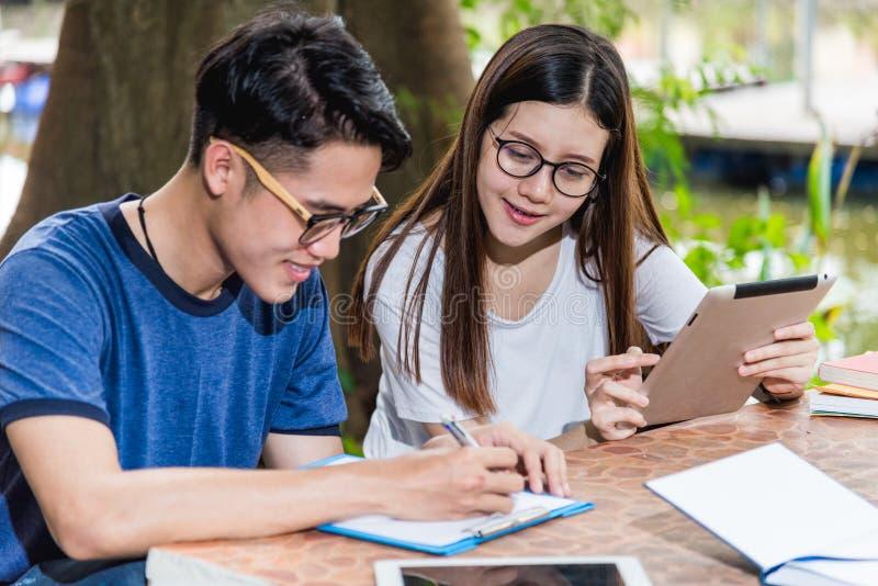 Gli studenti e l'amica dell'uomo sono durante le informazioni della lettura da fotografia stock