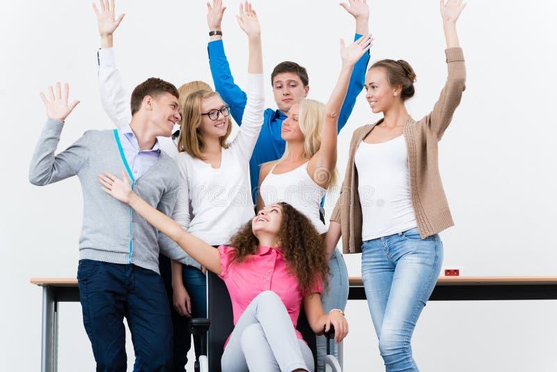 Gli studenti nella classe hanno sollevato le loro mani immagine stock libera da diritti